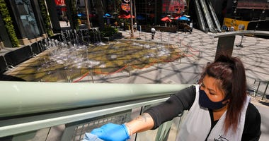 FILE - In this Thursday, June 11, 2020 file photo, Andrea Castaneda cleans the railings at Universal CityWalk near Universal City, Calif.
