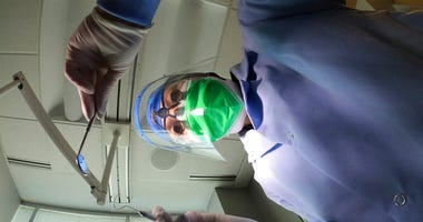 Dr. Terri Tiersky poses for a portrait in full personal protective equipment, double mask, face shield, gown and gloves, at her dentist office in Skokie, Ill., on Friday, June 12, 2020.