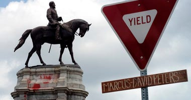 The graffiti-smeared statue of Robert E. Lee and Traveller stand behind a traffic sign with Marcus-David Peters Circle on a handwritten sign below on the circle that surrounds the monument on Monument Avenue in Richmond, Va., Wednesday, June 10, 2020.