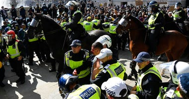 A wounded member of a far-right group is escorted by British police officers in riot gear, during scuffles as police tries to contain a protest at Trafalgar Square in central London, Saturday, June 13, 2020.