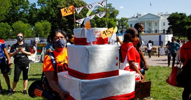A protester carries a mock birthday cake for President Donald Trump on Trump's birthday, Sunday, June 14, 2020, in Lafayette Park near the White House in Washington.