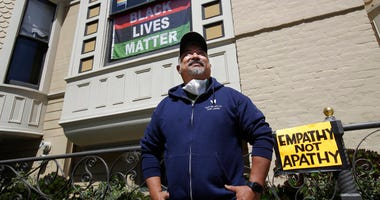 """James Juanillo poses outside of his home in San Francisco, Sunday, June 14, 2020. The CEO of a cosmetic company issued an apology Sunday after she and her husband confronted Juanillo and threatened to call police because he stenciled """"Black Lives Matter"""""""