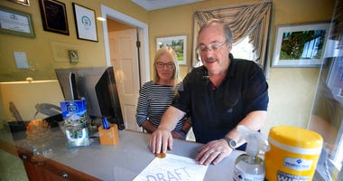 In this Wednesday, June 10, 2020, photo, Cod Cove Inn owners Ted and Jill Hugger show a draft of a compliance form that inn owners may be required to have out-of-state guests sign before being allowed to check in at their inn in Edgecomb, Maine.