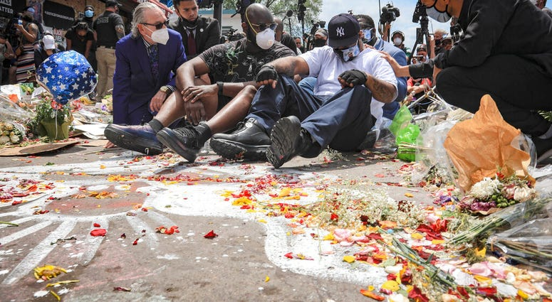 FILE - in this June 1, 2020 file photo, an emotional Terrence Floyd, second from right, is comforted as he sits at the spot at the intersection of 38th Street and Chicago Avenue, Minneapolis, Minn., where his brother George Floyd, encountered police and d