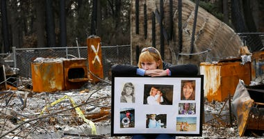 FILE - In this Feb. 7, 2019, file photo, Christina Taft, the daughter of Camp Fire victim Victoria Taft, displays a collage of photos of her mother, at the burned out ruins of the Paradise, Calif., home where she died in 2018.