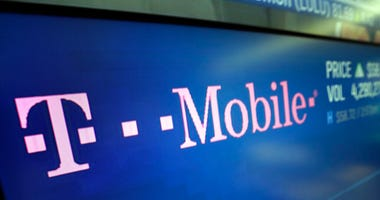 In this Feb. 14, 2018, photo, the logo for T-Mobile appears on a screen at the Nasdaq MarketSite in New York. T-Mobile, one of the three largest mobile carriers in the U.S., said it's working to fix a widespread network issue.