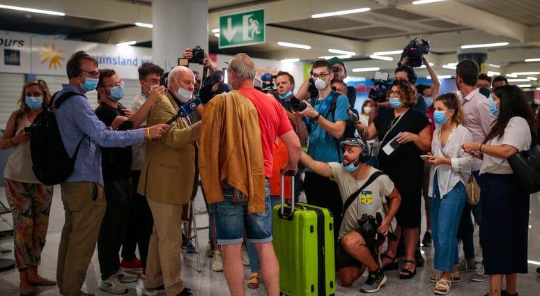A TUI X3 2312 Duesseldorf-Mallorca flight passenger talks to the press at Son Sant Joan airport in Palma de Mallorca, Spain, Monday, June 15, 2020.