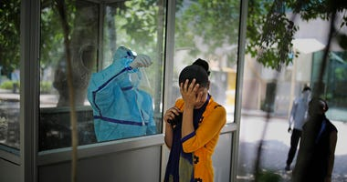 A woman reacts after getting a nasal swab taken to test for the coronavirus in Noida, on the outskirts of New Delhi, India, Tuesday, June 16, 2020.