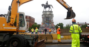 Workers for The Virginia Department of General Services install concrete barriers around the statue of Confederate General Robert E. Lee on Monument Avenue Wednesday June 17, 2020, in Richmond, Va.
