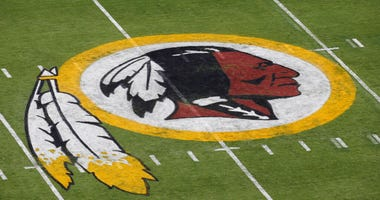 FILE - In this Aug. 7, 2014 file photo, the Washington Redskins NFL football team logo is seen on the field before an NFL football preseason game against the New England Patriots in Landover, Md.