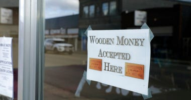 In this May 21, 2020 photo, a sign on a business in Tenino, Wash. says they will be accepting wooden money.