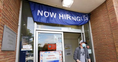 FILE - In this June 4, 2020, file photo, a customer walks out of a U.S. Post Office branch and under a banner advertising a job opening, in Seattle.