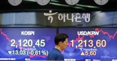 A currency trader walks by the screens showing the Korea Composite Stock Price Index (KOSPI), left, and the foreign exchange rate between U.S. dollar and South Korean won at the foreign exchange dealing room in Seoul, South Korea, Friday, June 19, 2020.