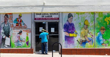 FILE - In this May 7, 2020 file photo, a person looks inside the closed doors of the Pasadena Community Job Center in Pasadena, Calif., during the coronavirus outbreak.