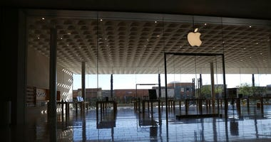 FILE - In this March 14, 2020 file photo, an Apple retail store is closed at a local mall in Scottsdale, Ariz.