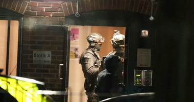 Armed police officers work at a block of flats off Basingstoke Road in Reading after an incident at Forbury Gardens park in the town centre of Reading, England, Saturday, June 20, 2020.