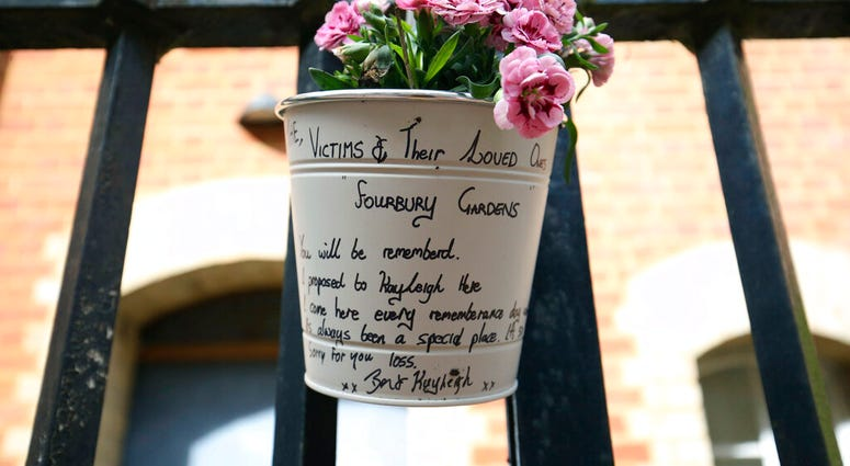 A floral tribute and message left at the Abbey gateway of Forbury Gardens following a multiple stabbing attack in the gardens, in Reading, England, Sunday June 21, 2020.