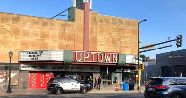 A police vehicle is parked outside the Uptown Theatre Sunday, June 21, 2020, following a shooting in Minneapolis' Uptown neighborhood. Multiple people were shot, one fatally, when gunfire broke out shortly after midnight Sunday.