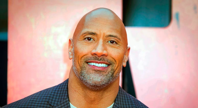 "FILE - In this April 11, 2018, file photo, actor Dwayne Johnson poses for photographers at the premiere of the ""Rampage,"" in London."