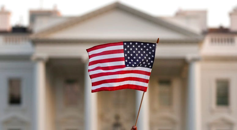 FILE - In this Sept. 5, 2017, file photo, a flag is waved outside the White House, in Washington.