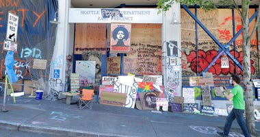 A person takes a photo of the Seattle Police East Precinct building, Monday, June 22, 2020, inside what has been named the Capitol Hill Occupied Protest zone in Seattle.