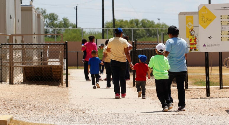 FILE - In this Aug. 23, 2019 file photo, immigrants seeking asylum hold hands as they leave a cafeteria at the ICE South Texas Family Residential Center in Dilley, Texas.