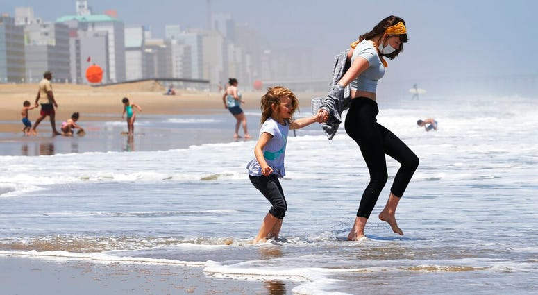 FILE - In this May 22, 2020, file photo, Victoria Faughnan, right, and Evelyn Faughnan, play in the surf in Virginia Beach, Va., the day the state reopened the beachfront during the coronavirus pandemic.