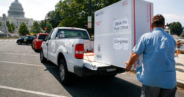 "Paul Falcon unloads a custom made ""Priority Mail"" box that organizers said contained two million signed petitions from postal customers asking Congress to approve emergency funding for the Postal Service, Tuesday, June 23, 2020, on Capitol Hill in Washing"
