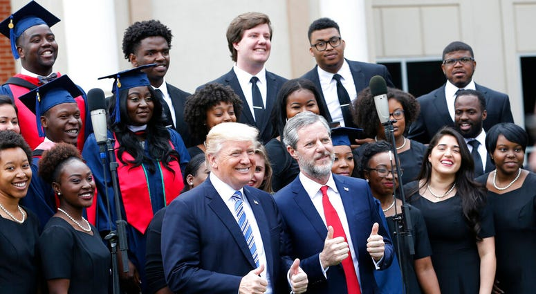 ILE - In this May 13, 2017 file photo, President Donald Trump poses with Liberty University president, Jerry Falwell Jr., center right, in front of a choir during of commencement ceremonies at the school in Lynchburg, Va.