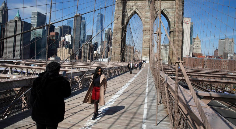 FILE - In this March 16, 2020 file photo, tourist Ines Tshiyomba, center, poses as her friend Garethe Mawonso takes her photo on the Brooklyn Bridge in New York.