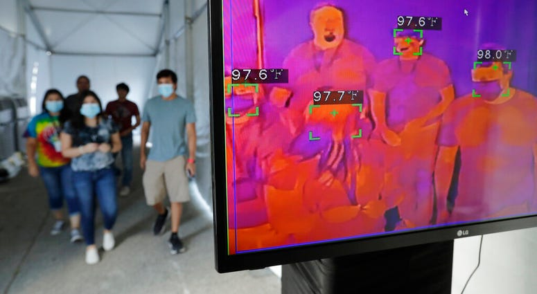 FILE - In this Friday, June 19, 2020 file photo, visitors to Six Flags Fiesta Texas pass through a thermal screening area as they enter the park as a precaution against COVID-19 in San Antonio.