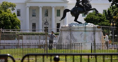 The base of the statue of former president Andrew Jackson is power washed inside a newly closed Lafayette Park, Wednesday, June 24, 2020, in Washington, which has been the site of protests over the death of George Floyd, a black man who was in police cust