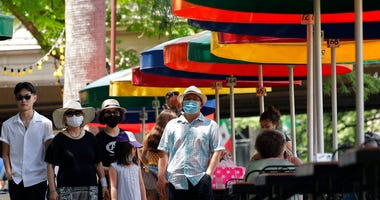 Visitors, some wearing masks to protect against the spread of COVID-19, walk along the River Walk in San Antonio, Wednesday, June 24, 2020, in San Antonio.