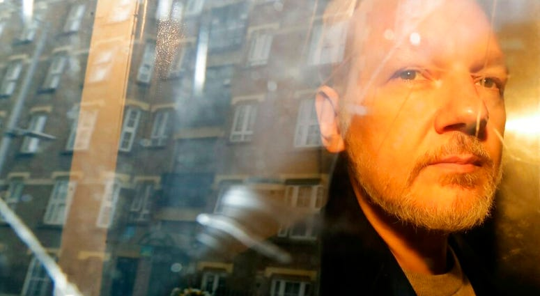 FILE - In this May 1, 2019, file photo, buildings are reflected in the window as WikiLeaks founder Julian Assange is taken from court in London.