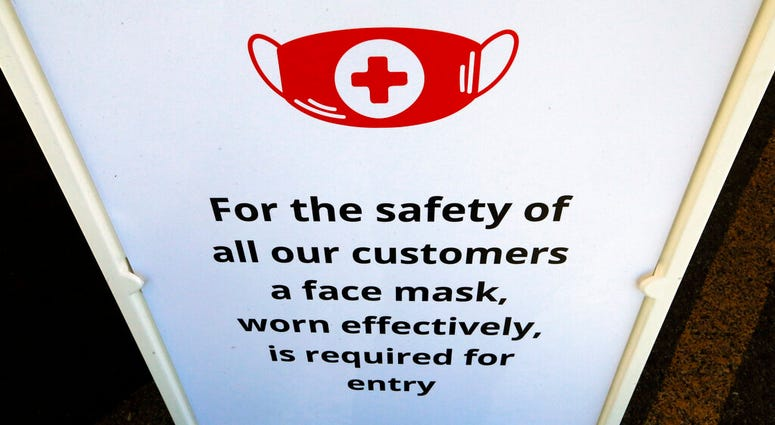 """In this Tuesday, June 23, 2020, photo, a """"Face Covering"""" sign is shown at Snider Bros. Meats, in Holladay, Utah."""