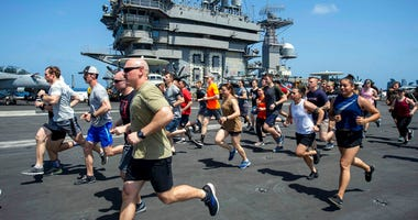In this May 24, 2020, photo, provided by the U.S. Navy Sailors run on the flight deck aboard the aircraft carrier USS Dwight D. Eisenhower (CVN 69).