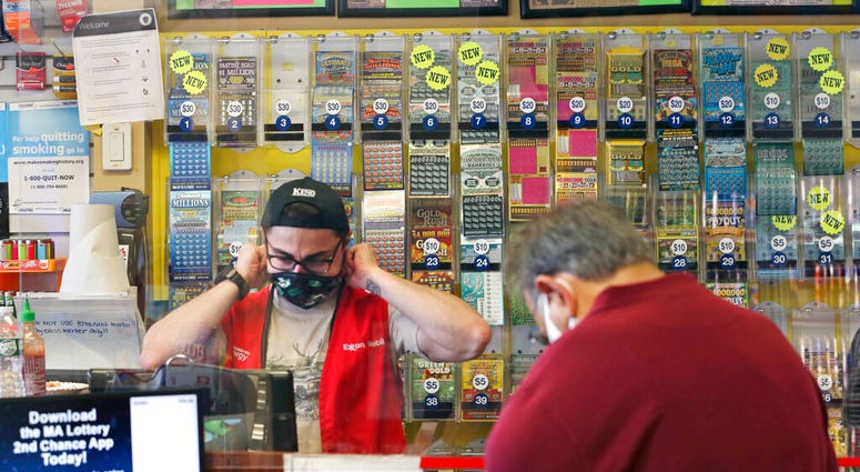 A clerk adjusts his protective mask while waiting on a masked customer at Ted's Stateline Mobil on Wednesday, June 24, 2020 in Methuen, Mass.