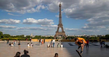 FILE - In this Monday, May 25, 2020 file photo, people stroll at Trocadero square near the Eiffel Tower in Paris.