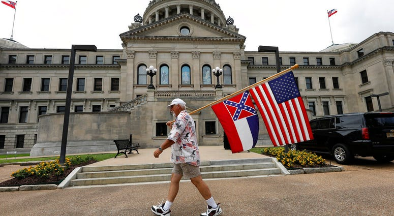 Don Hartness of Ellisville, walks around the Capitol carrying the current Mississippi state flag and the American flag, Saturday, June 27, 2020, in Jackson, Miss.