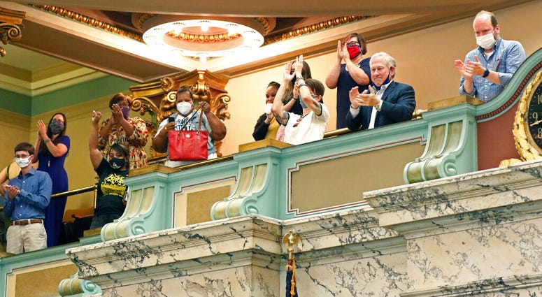 The gallery of the Mississippi Senate rise and applaud after the body passed a resolution that would allow lawmakers to change the state flag Saturday, June 27, 2020, at the Capitol in Jackson, Miss.