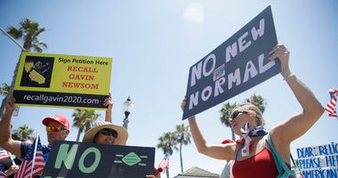 Demonstrators hold signs as they protest the lockdown and wearing masks Saturday, June 27, 2020, in Huntington Beach, Calif.