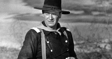 "FILE - In this undated photo, John Wayne appears during the filming of ""The Horse Soldiers."" In the latest move to change place names in light of U.S. racial history, leaders of Orange County's Democratic Party are pushing to drop film legend Wayne's name"