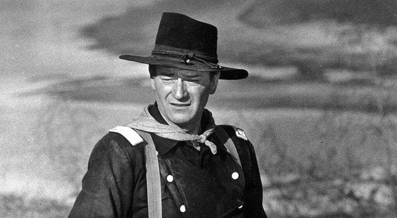 """FILE - In this undated photo, John Wayne appears during the filming of """"The Horse Soldiers."""" In the latest move to change place names in light of U.S. racial history, leaders of Orange County's Democratic Party are pushing to drop film legend Wayne's name"""