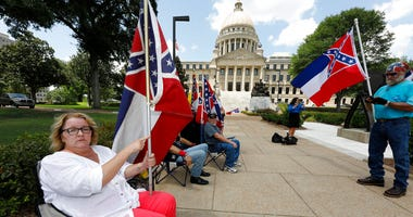 essa Collett of Petal, left, wants her vote to count as she supports the current flag as do other supporters standing outside the state Capitol in Jackson, Miss., Sunday, June 28, 2020.