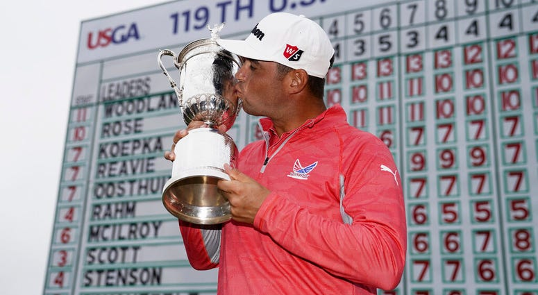 FILE - In this June 16, 2019, file photo, Gary Woodland poses with the trophy after winning the U.S. Open golf tournament in Pebble Beach, Calif.
