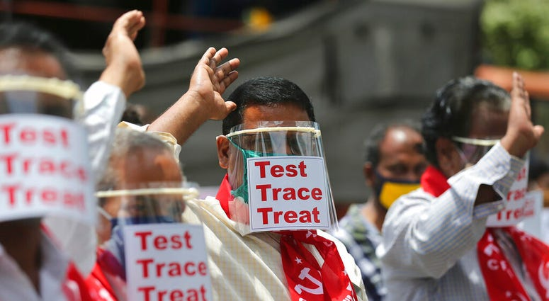 Activists of Communist Party of India Marxist display placards on face shields and shout slogans during a protest asking the state government to increase testing and free treatment for all COVID-19 patients in Hyderabad, India, Monday, June 29, 2020.