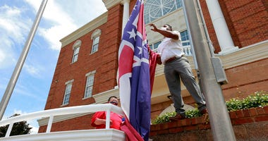 In this Monday, June 29, 2020, City of Tupelo Community Outreach Coordinator Marcus Gary takes down the Mississippi state flag that flew over the City Hall of Tupelo one last time Monday, June 29, 2020.