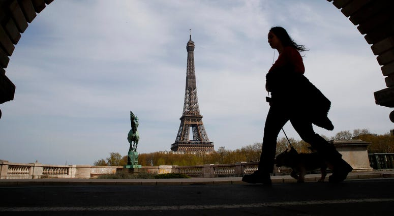 FILE - In this Tuesday, April 7, 2020 file photo, a woman walks her dog on a Paris bridge, with the Eiffel tower in background, during a nationwide confinement to counter the COVID-19.