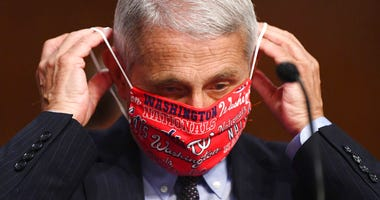 Dr. Anthony Fauci, director of the National Institute for Allergy and Infectious Diseases, lowers his face mask as he prepares to testify before a Senate Health, Education, Labor and Pensions Committee hearing on Capitol Hill in Washington, Tuesday, June