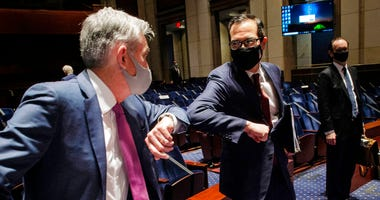 Federal Reserve Board Chairman Jerome Powell, left, and Treasury Secretary Stephen Mnuchin, bump elbows at the conclusion of a House Committee on Financial Services hearing on oversight of the Treasury Department and Federal Reserve pandemic response, Tue